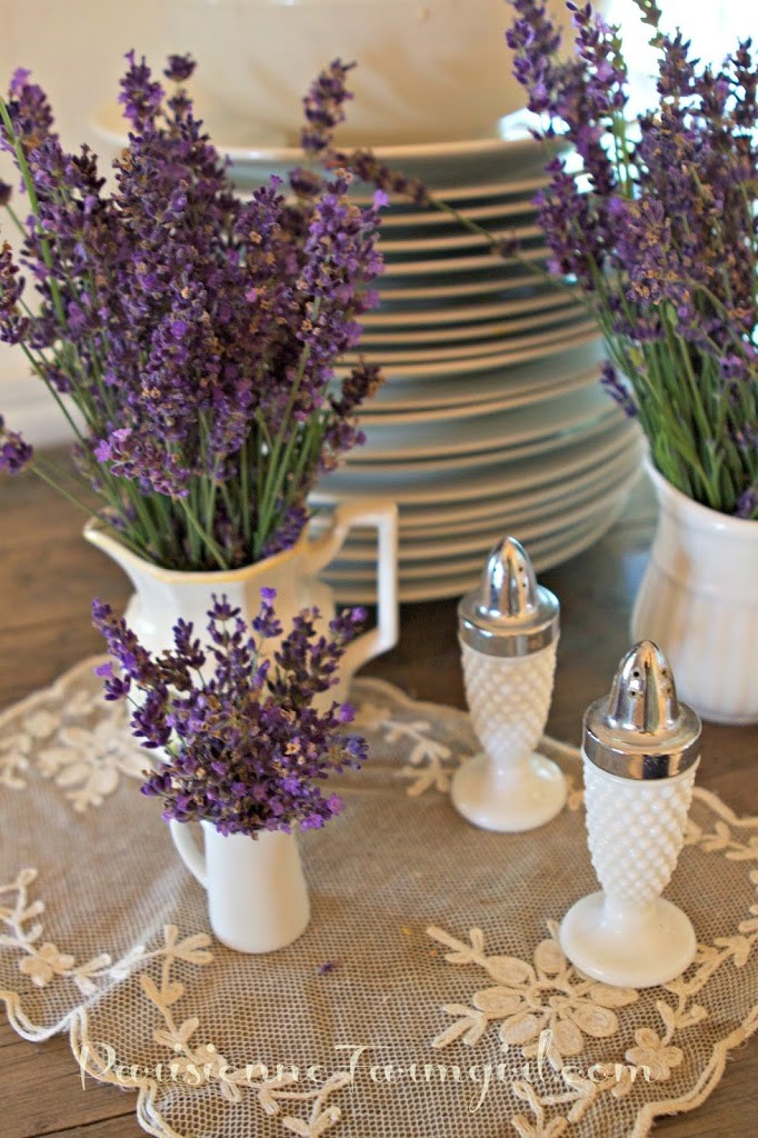 lavender sprigs in bowls on table with plates and lace