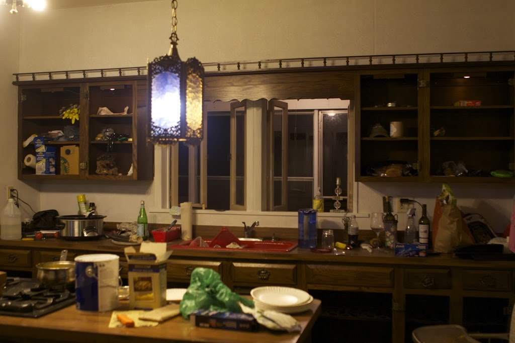 view of a messy kitchen with dark cabinets